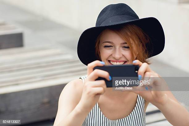 woman smiling and taking a picture with her phone