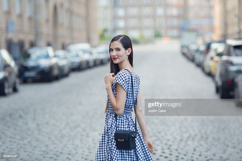 woman smiling and turning back at us in the street : Stock Photo