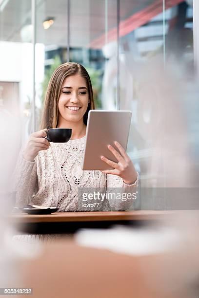 Mujer sonriendo y usando tableta digital en Café
