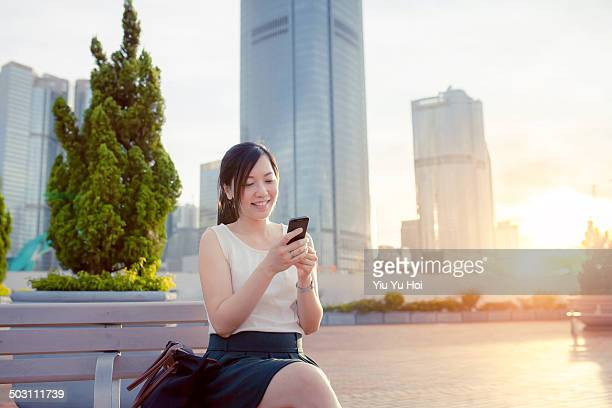 woman smiling as she is using smartphone in city - yiu yu hoi stock pictures, royalty-free photos & images
