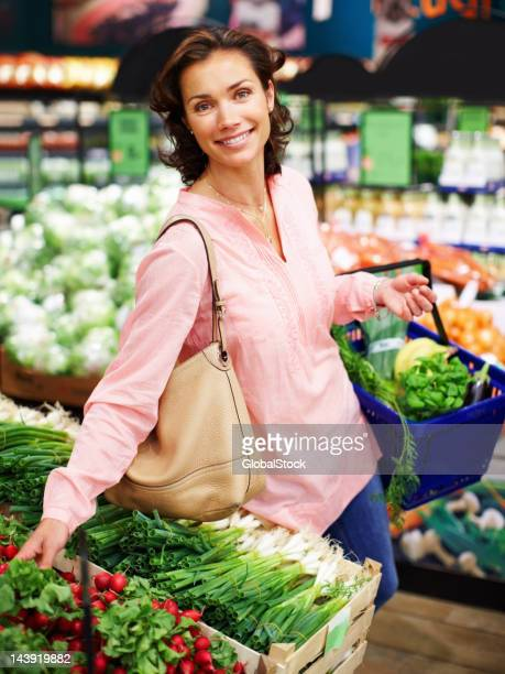 Woman smiling as she shops for fresh vegetables