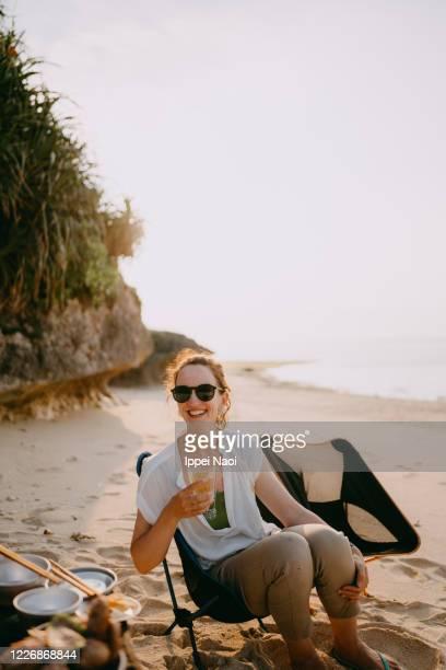 woman smiling at camera on beach at sunset - キャンプ 1人 ストックフォトと画像