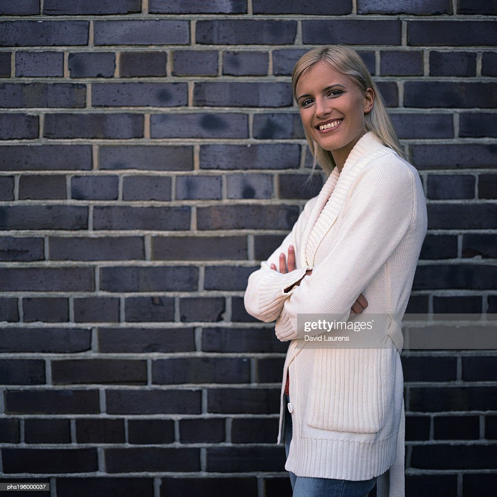 Woman smiling at camera, standing next to brick wall. : Stockfoto