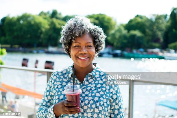 woman smiling at camera with smoothie - town stock pictures, royalty-free photos & images