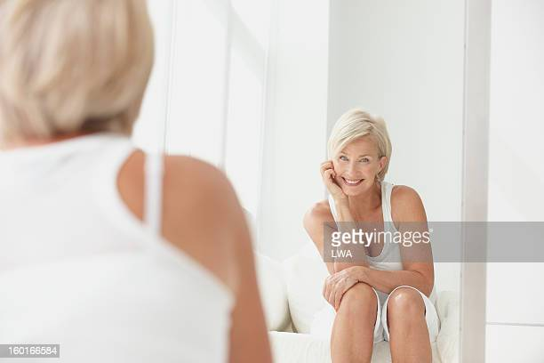 Woman smiling at herself in mirror