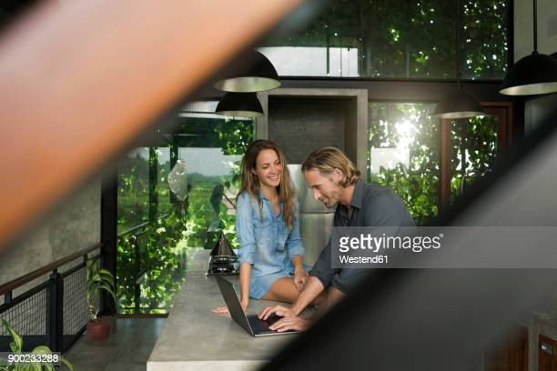 woman smiling at husband with laptop in modern minimalist kitchen in contemporary design house - premium access stock pictures, royalty-free photos & images