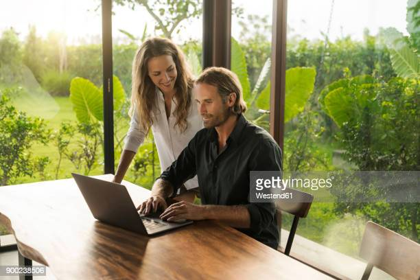 woman smiling at husband working on laptop in design house surrounded by lush tropical garden - 30 39 years photos stock photos and pictures