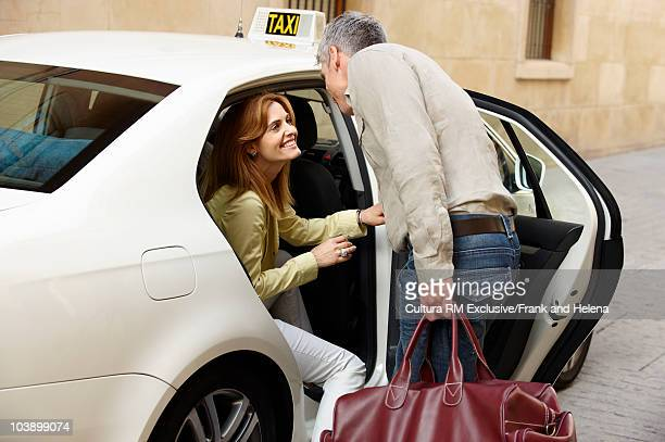 Woman smiling at man from back of taxi