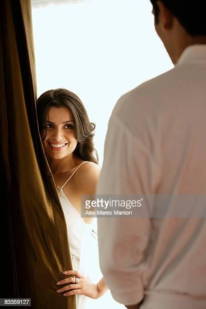 woman smiling at man from behind curtain