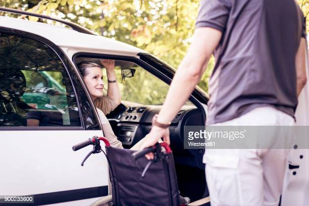 Woman smiling at man outside car holding wheelchair