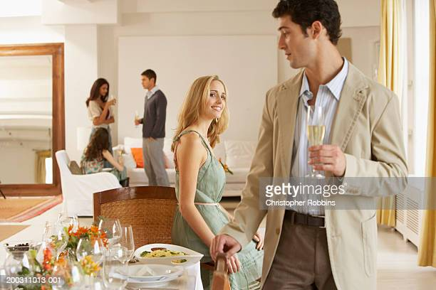 woman smiling at man standing by dining table, friends in background - love at first sight stock pictures, royalty-free photos & images
