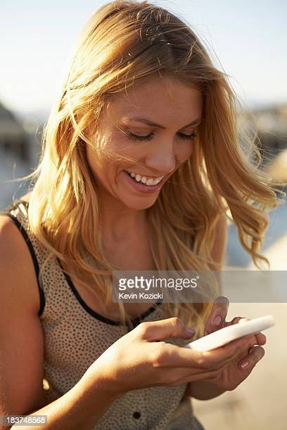 Woman smiling at text message on mobile phone
