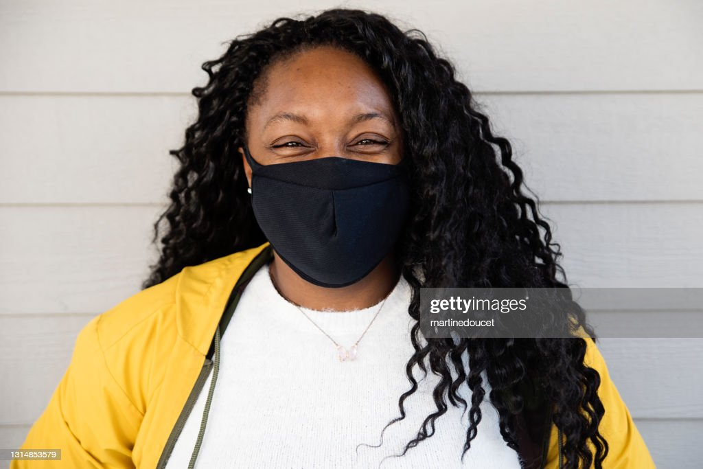 Woman smiling behind protective mask outdoors. : Stock Photo