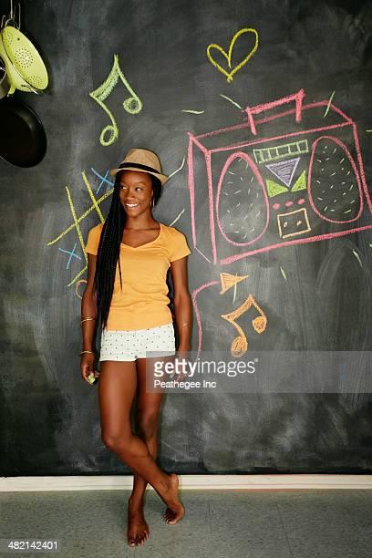 Woman smiling by blackboard wall