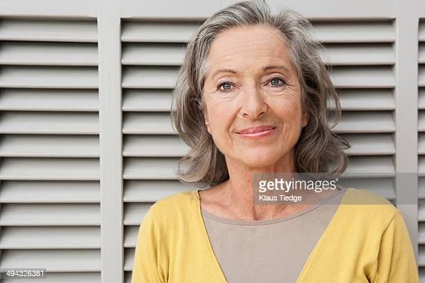 woman smiling by shutters - 60 64 years stock pictures, royalty-free photos & images