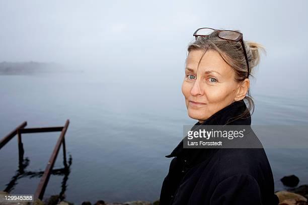 woman smiling by still lake - 50 54 jaar stockfoto's en -beelden