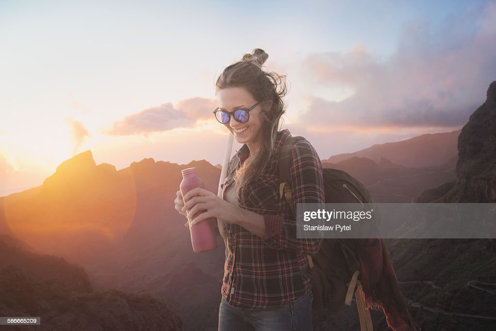 Woman smiling, drinking water in mountains : Stock Photo