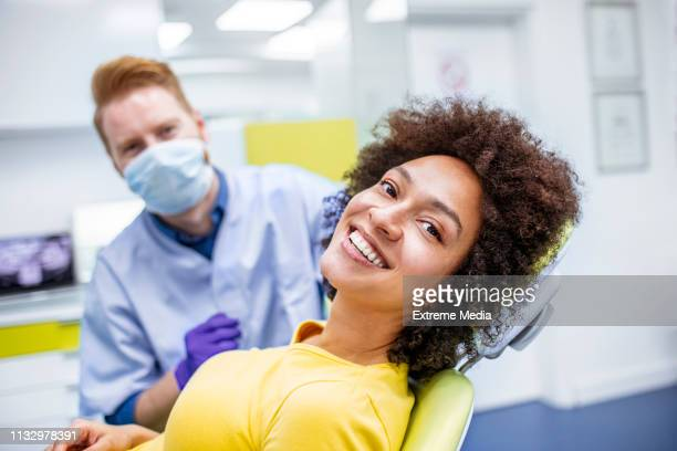 woman smiling during dental checkup - dentist stock pictures, royalty-free photos & images