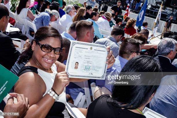 A woman smiling holding a Certificate of Naturalization at the Oath of Citizenship Ceremony