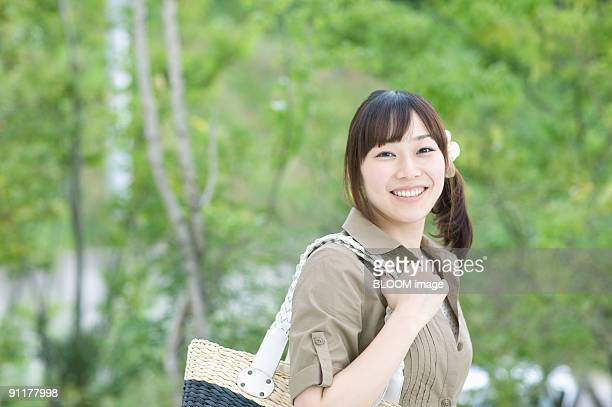 Woman smiling, holding bag