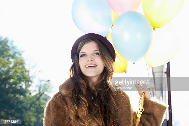 woman smiling holding balloons