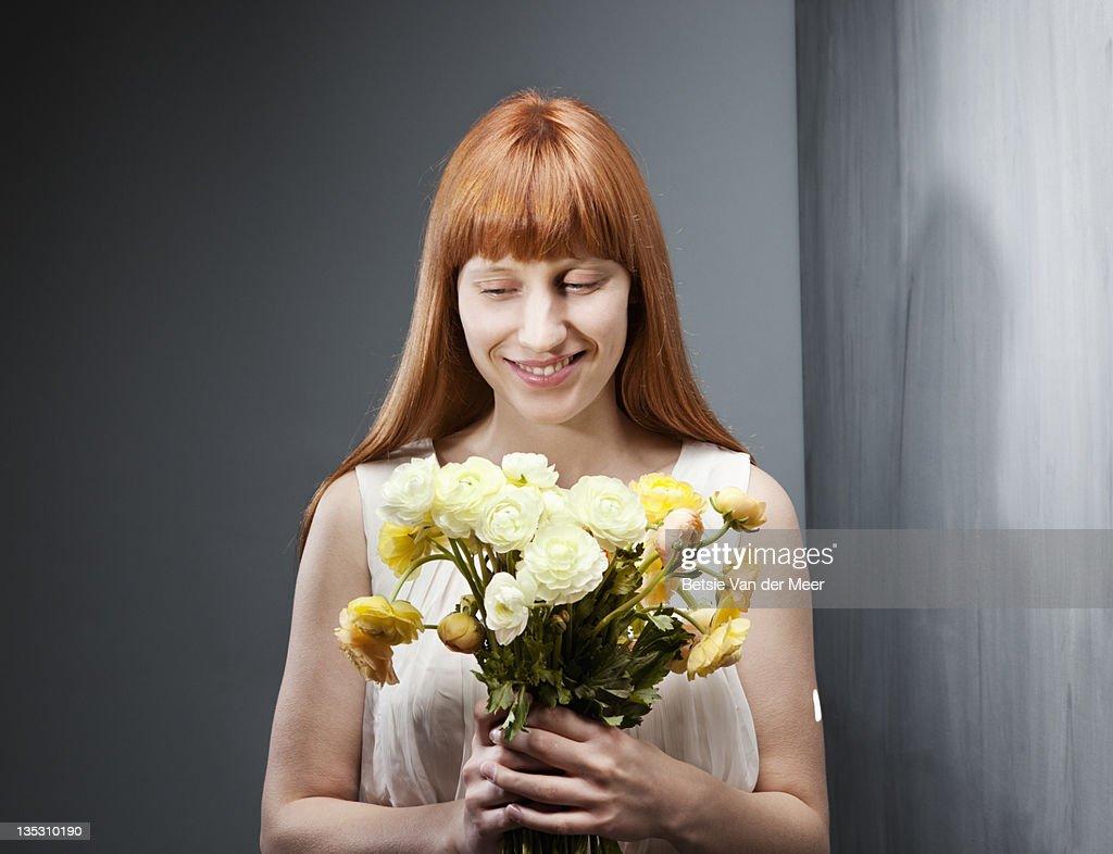Woman smiling, holding bouquet of flowers. : Foto de stock