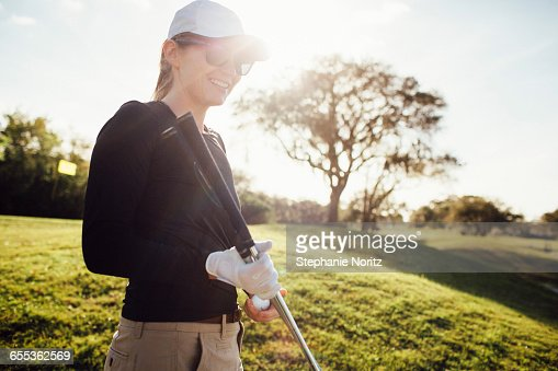 Woman smiling holding golf clubs on golf course