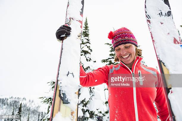 Woman Smiling & Holding Skis in the Snow
