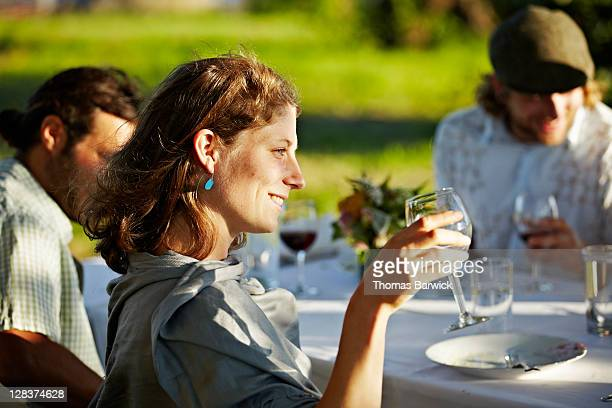 Woman smiling holding wine glass up to toast