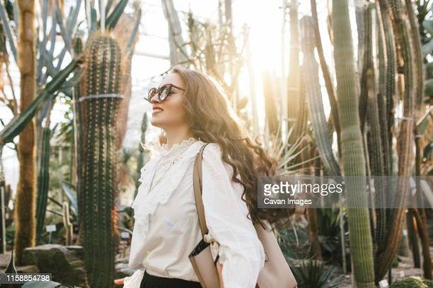 woman smiling in a botanical garden - botanical garden stock pictures, royalty-free photos & images