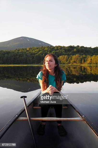 woman smiling in a canoe on a lake in mountains