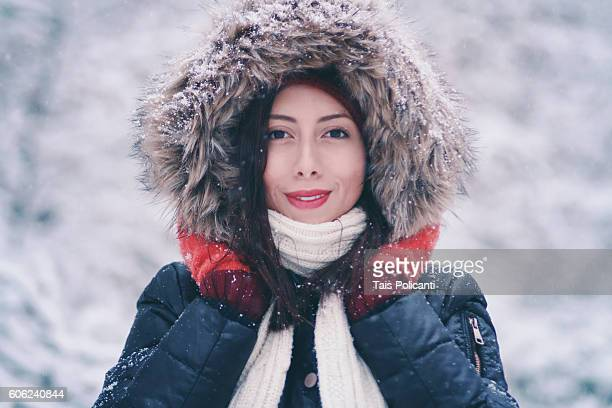 woman smiling in a snowy forest while snowing, munich, germany - winter coat stock pictures, royalty-free photos & images