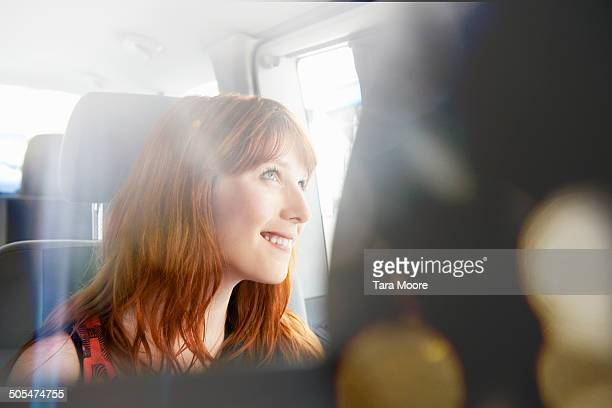 woman smiling in car looking out window