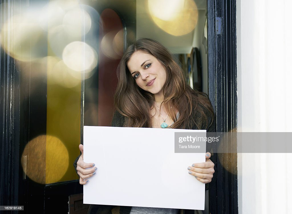 woman smiling in doorway with blank sign : Stock-Foto