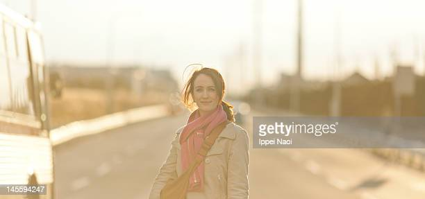 woman smiling in middle of road at sunset - 後ろボケ ストックフォトと画像