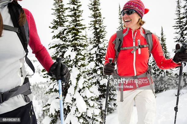Woman Smiling in mountains holding ski poles