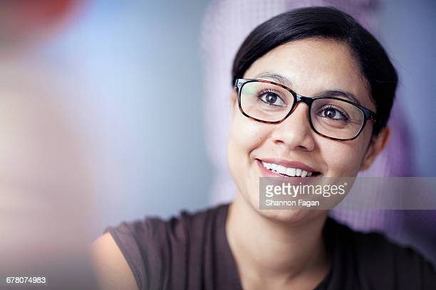 Woman smiling in office with colleagues in meeting