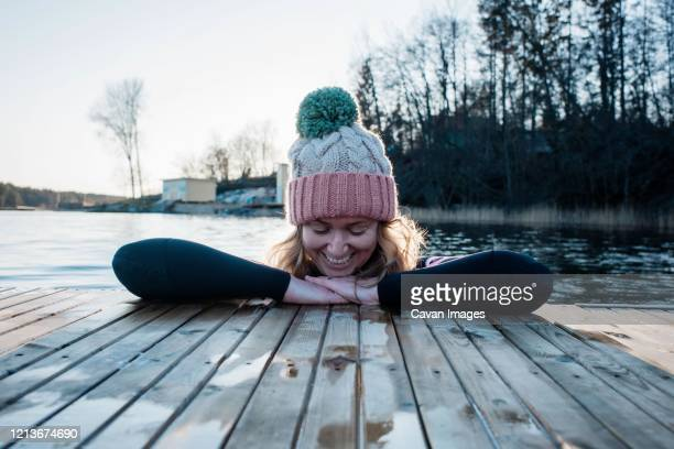 woman smiling leaning on a jetty whilst in the sea cold water swimming - ponton photos et images de collection