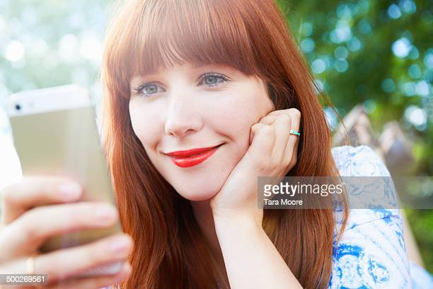 woman smiling looking at mobile in park