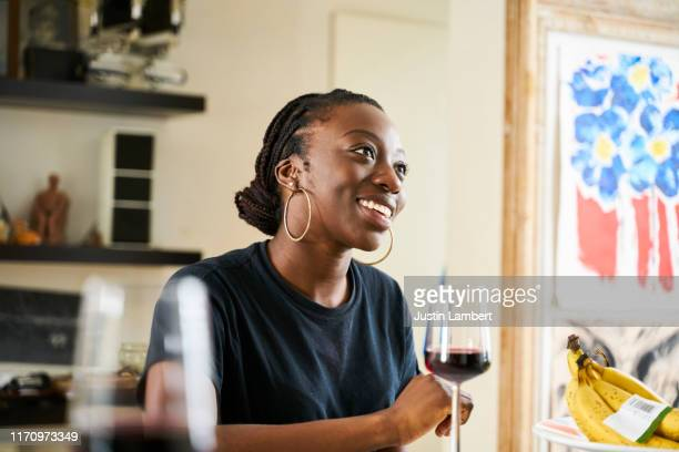 woman smiling looking off camera at friends drinking wine in the kitchen - wine stock pictures, royalty-free photos & images