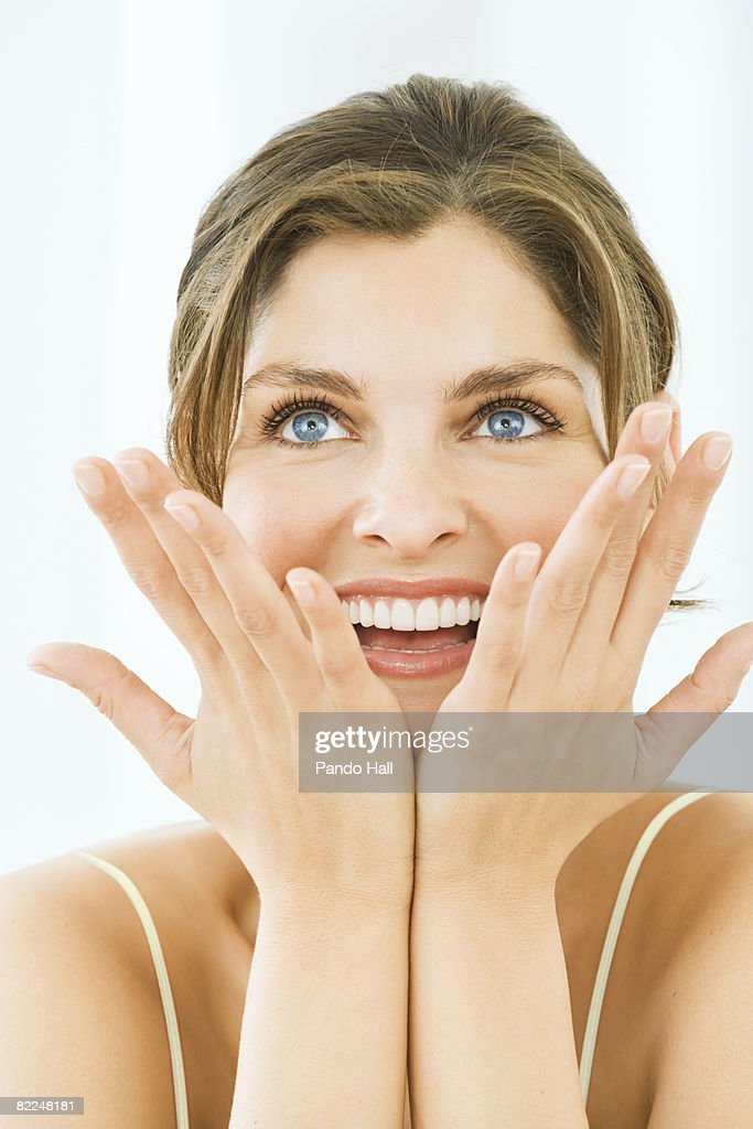 Woman smiling, looking up, hands on chin : Stock Photo