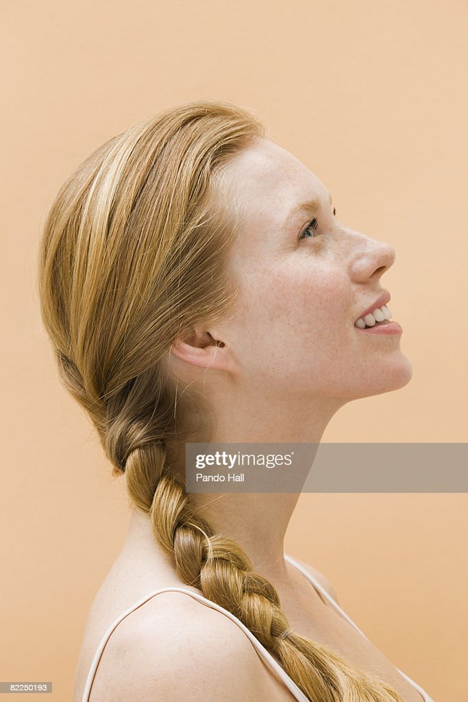 Woman smiling, looking up, side view : Stock Photo