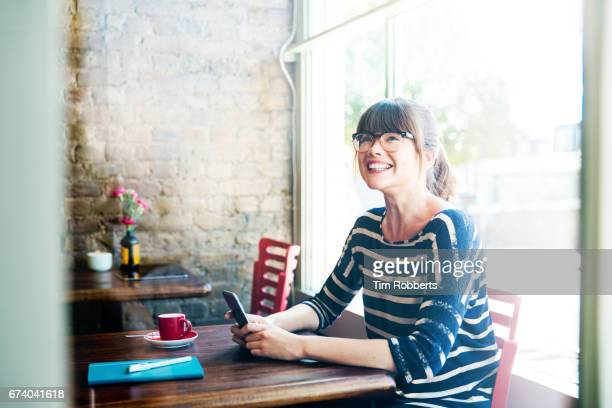 Woman smiling looking up with phone in coffee shop