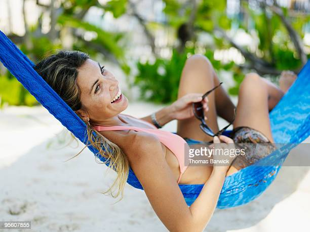 Woman smiling lying in hammock holding sunglasses