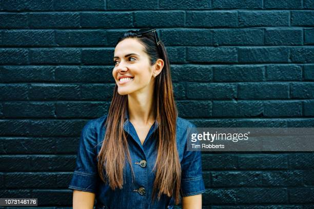 woman smiling off camera - denim dress stock photos and pictures