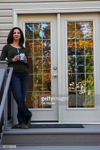 Woman smiling on back porch with cup