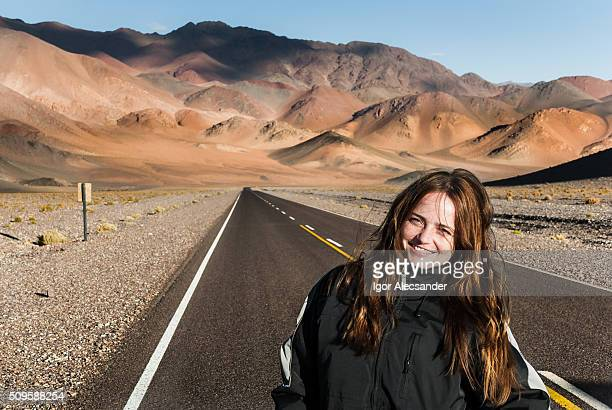 Woman smiling on desert road, Paso de San Francisco, Argentina Chile borderline, Andes, Fiambala, Catamarca, Argentina