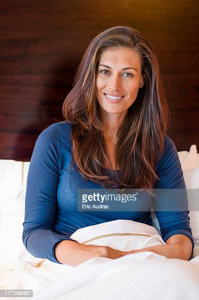 woman smiling on the bed in a hotel room - mid adult women stock pictures, royalty-free photos & images