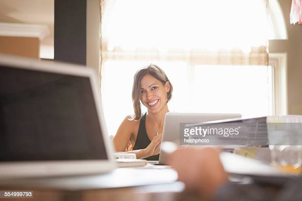 woman smiling over her work at home - heshphoto stock pictures, royalty-free photos & images