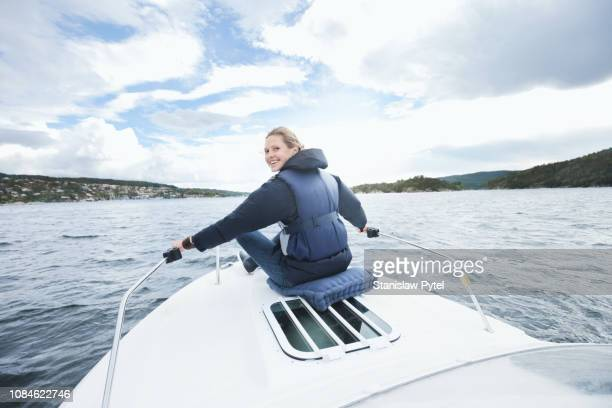 woman smiling, sitting on boats bow - navy blue stock pictures, royalty-free photos & images